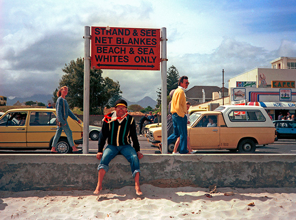 """Allan Boesak at a beach demonstration in 1989. The image was included in the Exhibition by Reney without her knowing, so I am told, that it was mine. It was my first year as a student at the University of Cape Town and I don't believe I even owned a camera. I am likely to have borrowed my brother's camera for the day. A group of us from UCT went to join the beach protest in Strand. It was August 1989 and beach protests had been organised on the """"whites only"""" beaches of Strand and Bloubergstrand. About 300 of us made it through to the Strand before a heavy police presence prevented any more protesters from reaching the beach. The police also prevented the press from getting there. I seemed to be the only one with a camera that day. Allan Boesak was there and he sat down under a sign that said """"Strand & See Net Blankes - Beach & Sea Whites Only"""". I took two shots of him alone beneath the sign before people piled in to be in the picture."""