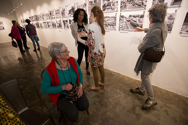 Black Sash activist and photographer, Gille De Vlieg converses with a fellow Black Sash member during the DocuFest Africa exhibition walkabout. Behind are images from the Tiso Blackstar (formerly Times Media) Collection.